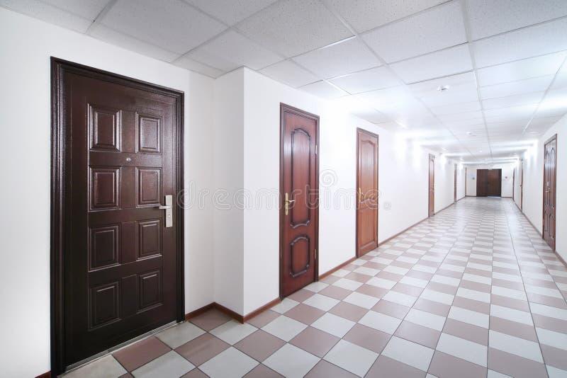Långt hall med bruna trädörrar arkivfoton