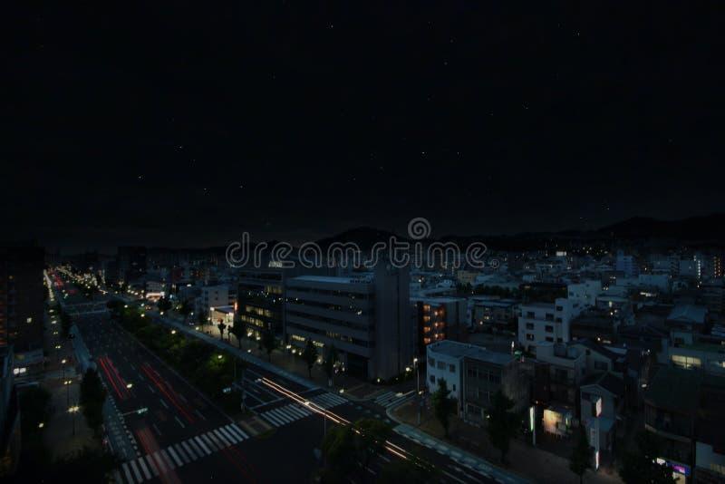 Långt ljus från bilen på vägen som kör i natten i staden och till himlen och stjärnorna royaltyfri foto