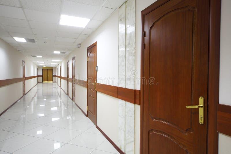 Långt ljust hall med trädörrar royaltyfri foto