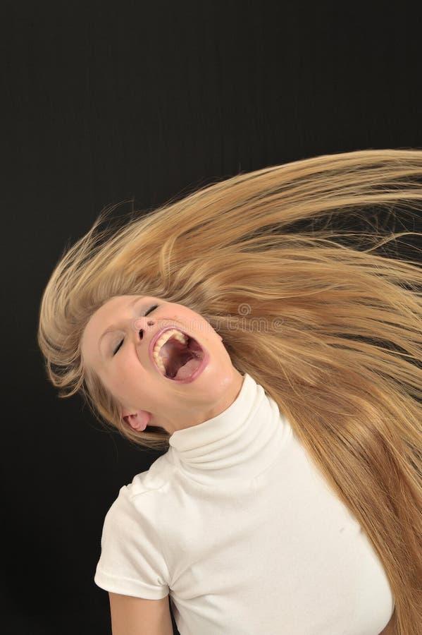 långt rop för angrily blont flickahår arkivfoto