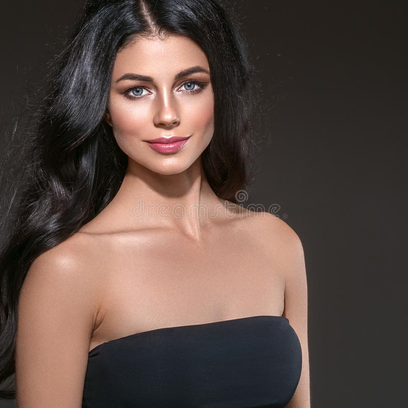 Långt svart hår för skönhetkvinna Härlig brunnsortmodellflicka med perfekt ny ren hud Brunettkvinna som ler på svart bakgrund arkivbild