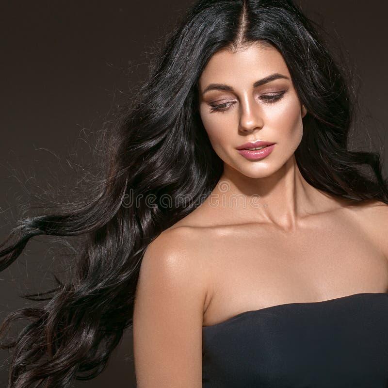 Långt svart hår för skönhetkvinna Härlig brunnsortmodellflicka med perfekt ny ren hud Brunettkvinna som ler på svart bakgrund royaltyfri fotografi