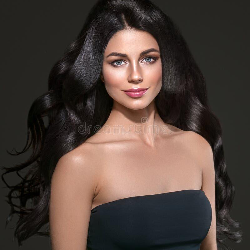 Långt svart hår för skönhetkvinna Härlig brunnsortmodellflicka med perfekt ny ren hud Brunettkvinna som ler på svart bakgrund royaltyfri bild