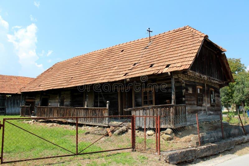 Långt träförfallet familjhus som överges av ägare och som är vänstert med den förstörda främre farstubron och brutna träbräden arkivfoton