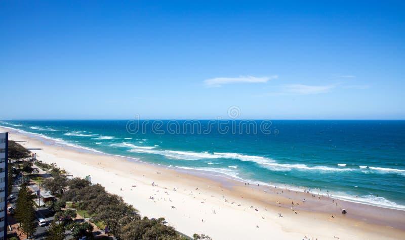 Långt vitt sandstrand och hav med vågor arkivbilder