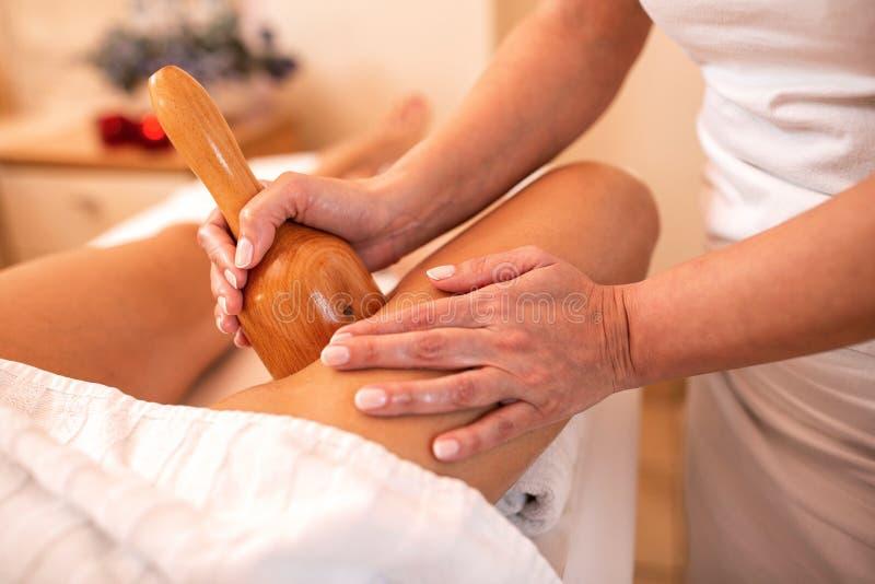 Lårmassage med ett handverktyg för massage royaltyfria bilder