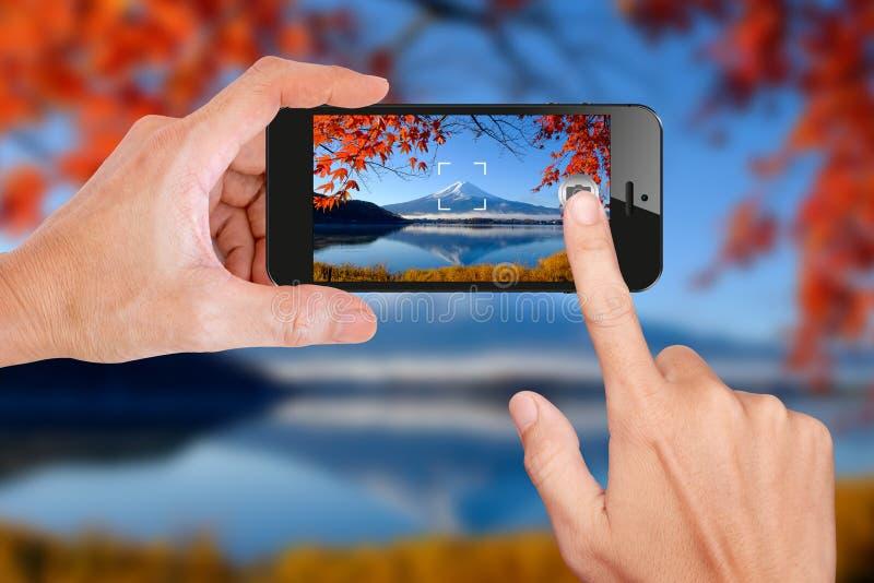 Låsa fast en bild av Mt Fuji i höst vid mobiltelefonen royaltyfri bild