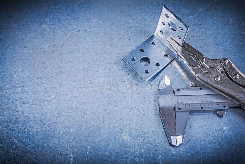 Låsa konsolen för vinkeln för klämman för käkeplattångnonieskalan på metallisk backgr royaltyfria foton