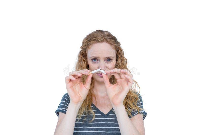 Låsande fast cigarett för allvarlig blond kvinna royaltyfri bild