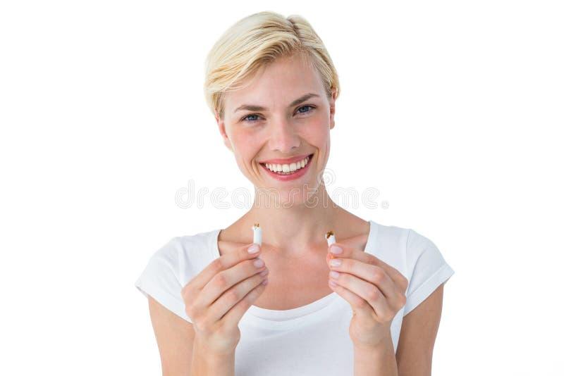 Låsande fast cigarett för attraktiv blond kvinna och le på kameran arkivbilder