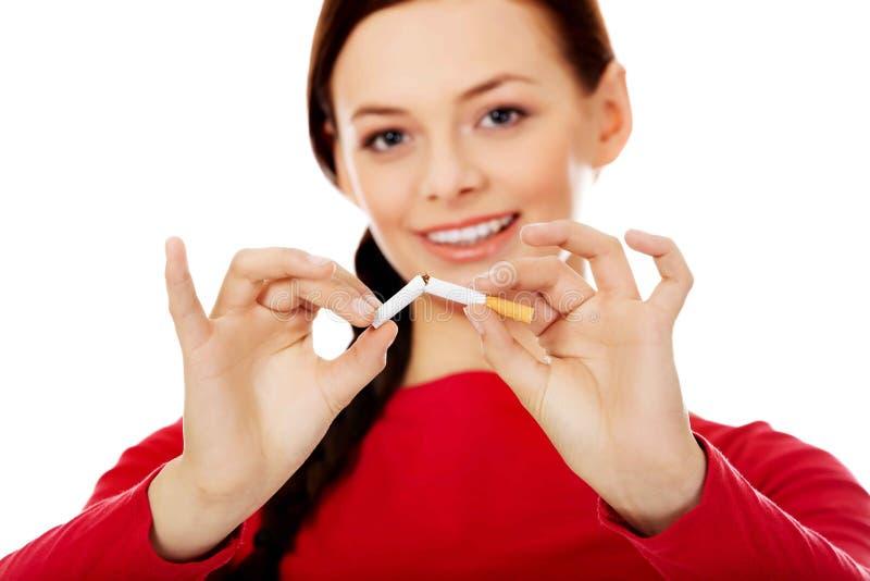 Låsande fast cigarett för lycklig studentkvinna royaltyfri fotografi