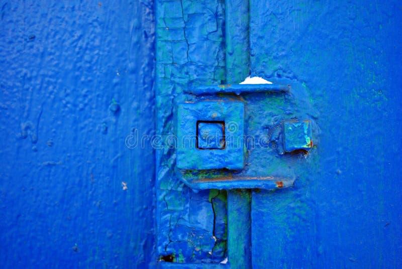 Låset på gammal järndörr med en sjaskig ljus blått målar, grungebakgrund arkivbild