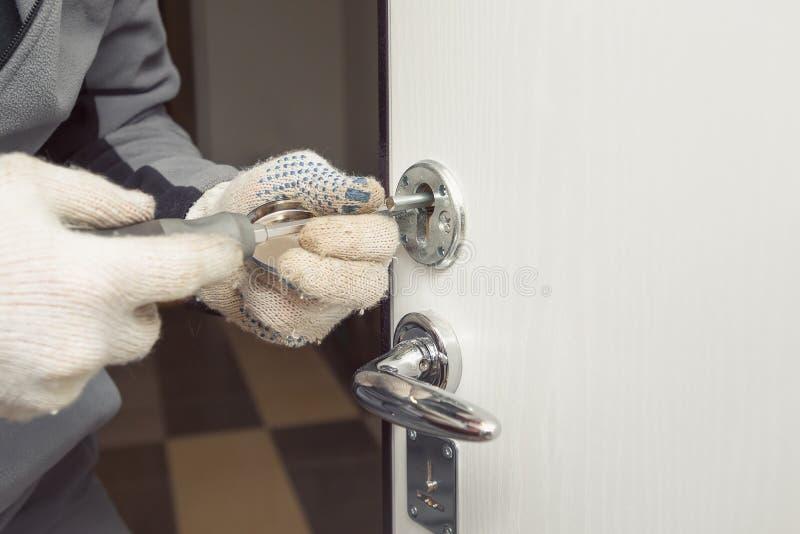 Låssmeden i trasahandskar ändrar dörrlåsen royaltyfri foto