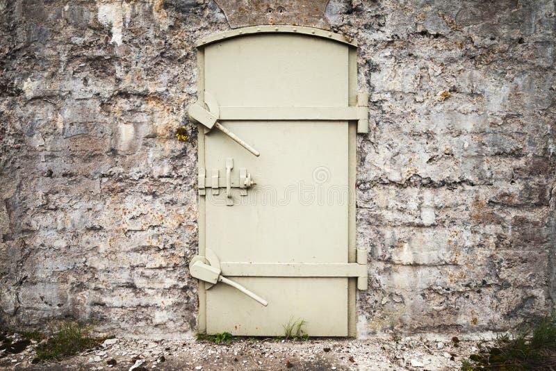 Låst massiv metalldörr i gammal vägg fotografering för bildbyråer