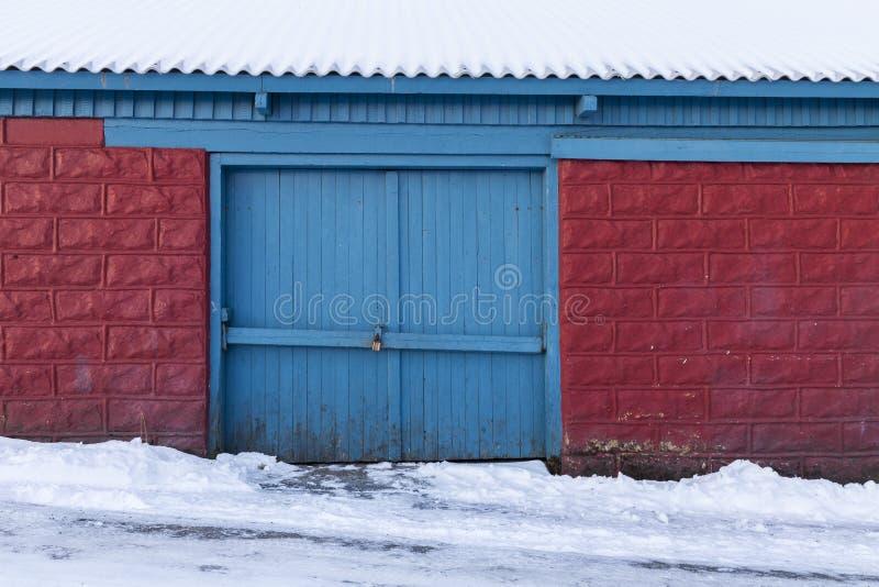 Låst port av det gamla träskjulet, röda tegelstenar med den blåa dörren i seger royaltyfri bild