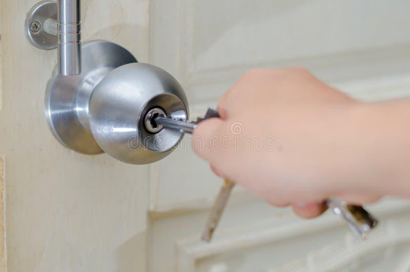 Låst upp knopphandbruk tangenten för att låsa knoppen för dörr för trädörr för dörr för dörrknopp den vita rostfria eller handtag arkivfoton