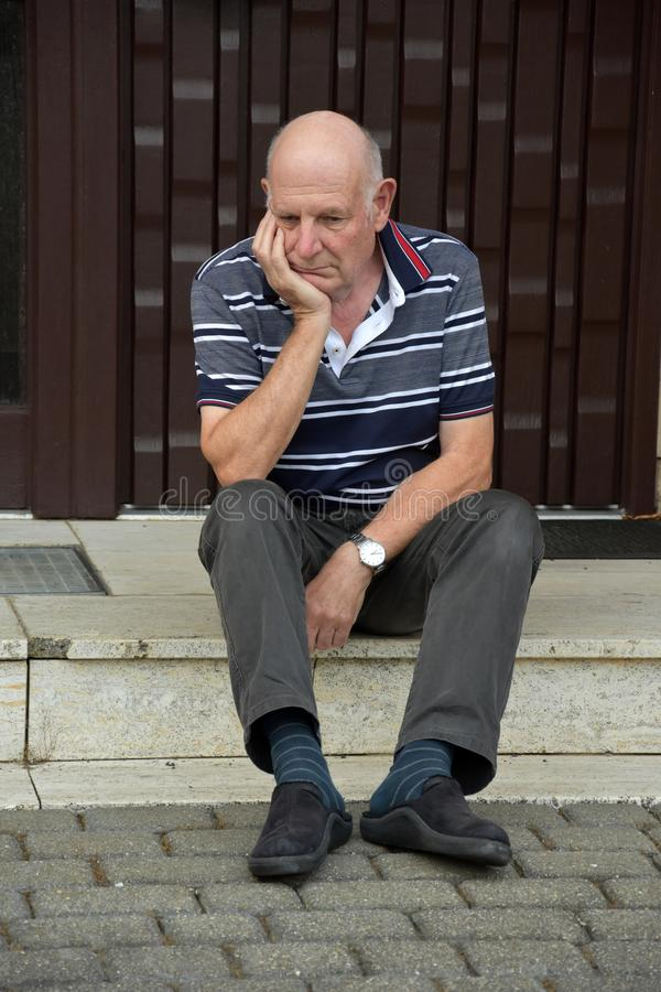 Låst ut hög man som framme sitter av hans hus royaltyfri foto