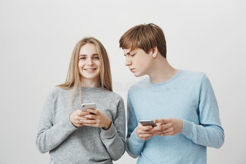 Låt mig se vad du skrev Stående av den bekymrade fokuserade unga mannen som kikar på flickvänsmartphonen, medan rymma arkivfoto