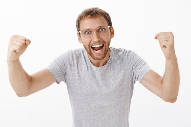 Låt oss bet dem Energized upphetsad och entusiastisk lagledare i exponeringsglas och den gråa t-skjortan som lyfter nävar i jubel arkivbild