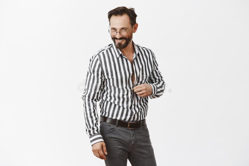 Låt oss fortsätta konversation i sovrumhonung Stående av den flirty stiliga vuxna mannen med skägget som knäpper upp skjortan och arkivfoto
