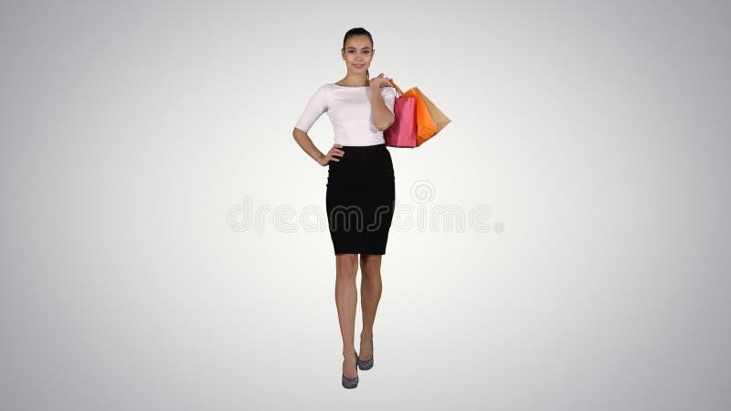 Låt oss gå att shoppa! Kvinna som går med shoppingpåsar på lutningbakgrund arkivbilder