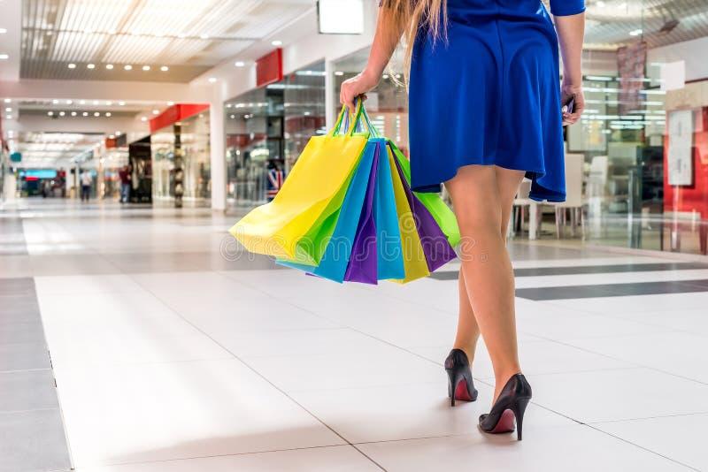 Låt oss gå att shoppa, kvinnliga ben med pappers- påsar i galleria royaltyfria bilder