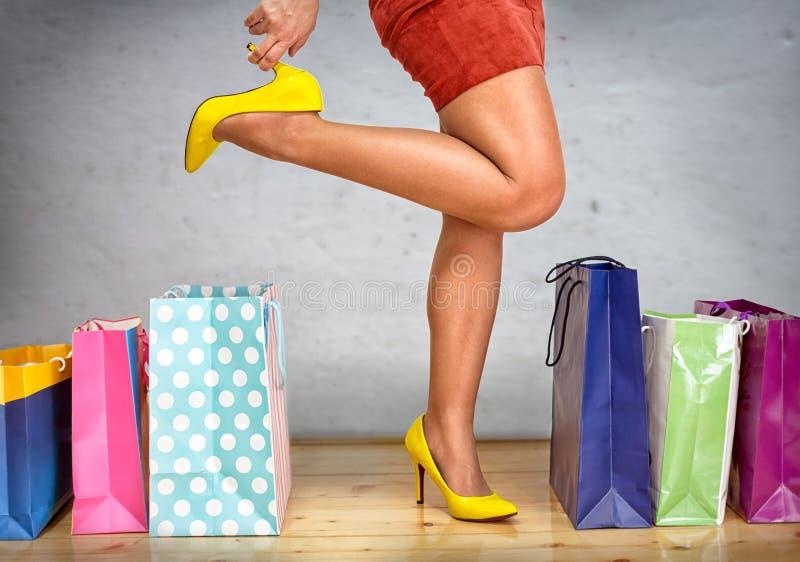 Låt oss gå att shoppa! Roliga posera kvinnaben i höga häl arkivbilder