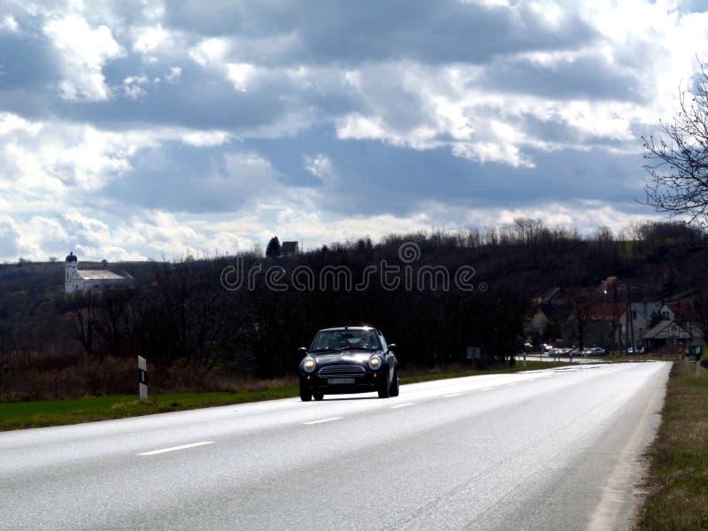 Låt oss köra! Asfaltera vägen i perspektiv med bilen, kyrkan & blå himmel arkivbilder