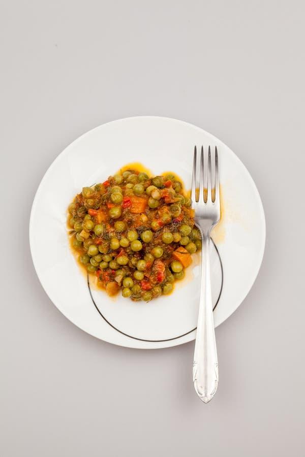 Låta småkoka med ärtor, morötter, lökar, tomatsås och kryddor royaltyfri bild