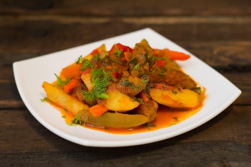 Låta småkoka med potatisar, morötter, knipor, tomater och varma peppar Azu vid Tartarian på en platta för vit fyrkant Trälantligt royaltyfri bild