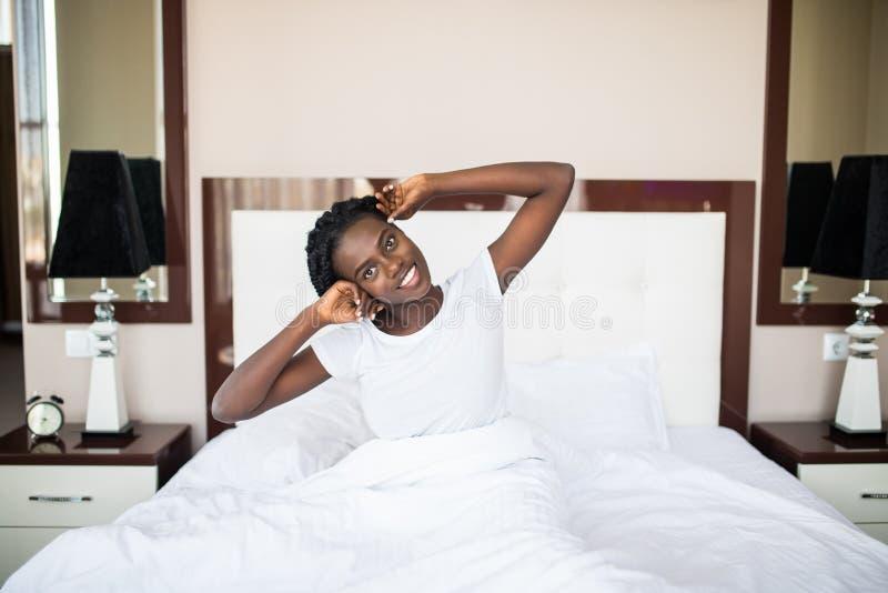 Låter ny dag för start Härlig ung afrikansk kvinna i ärmlös tröja som ligger i säng och sträcker hennes armar arkivbilder
