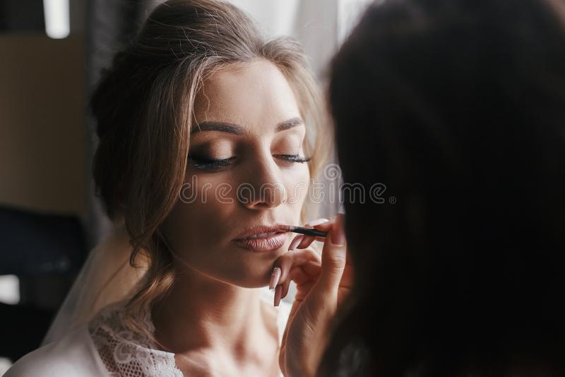 Lèvres de peinture de maquilleur avec le rouge à lèvres nu sur le visage c de la jeune mariée photo libre de droits