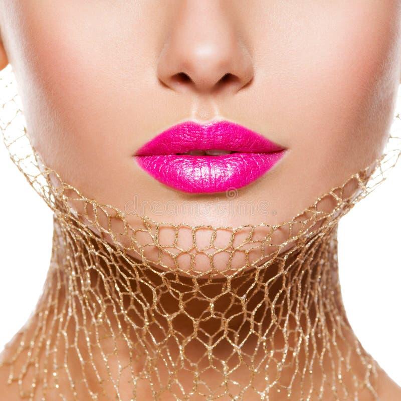 Lèvres femelles avec le rouge à lèvres rose et le voile d'or sur le cou clos photo stock