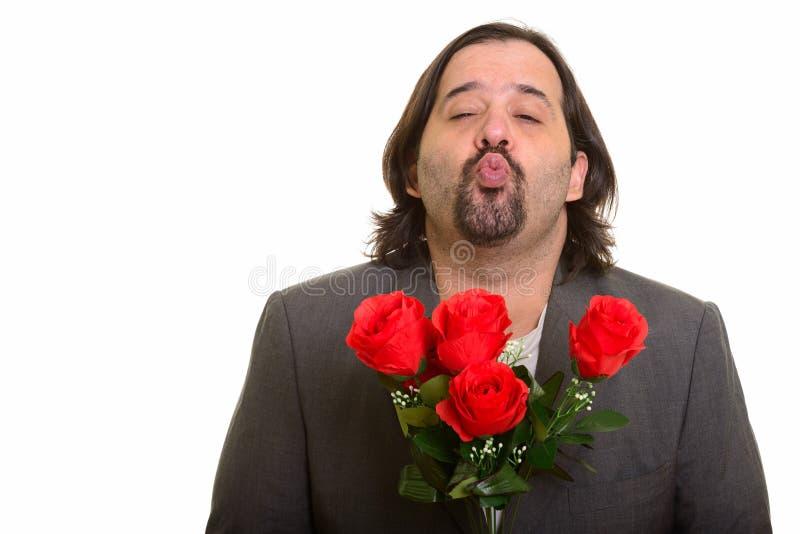 Lèvres froissantes de gros homme d'affaires caucasien tout en tenant les roses rouges photo stock