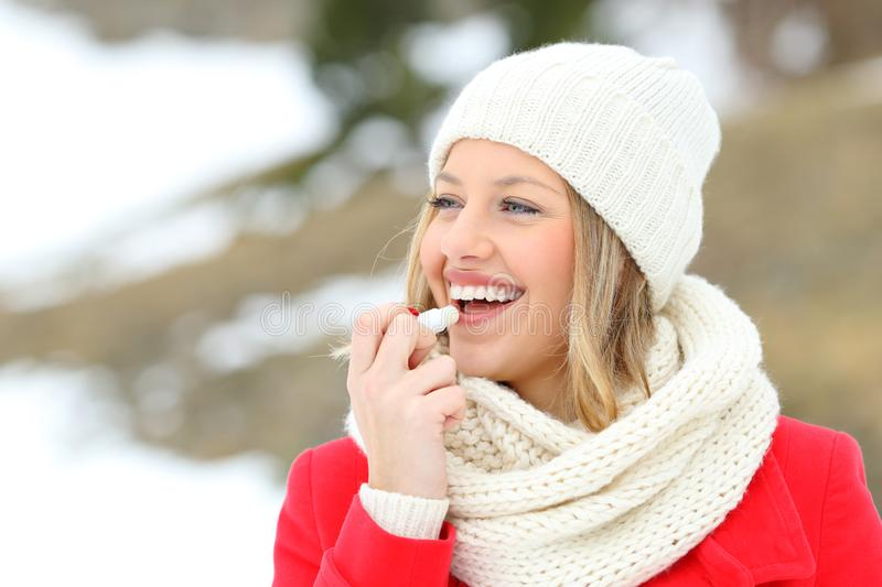 Lèvres protectrices de fille avec le baume à lèvres en hiver photo libre de droits