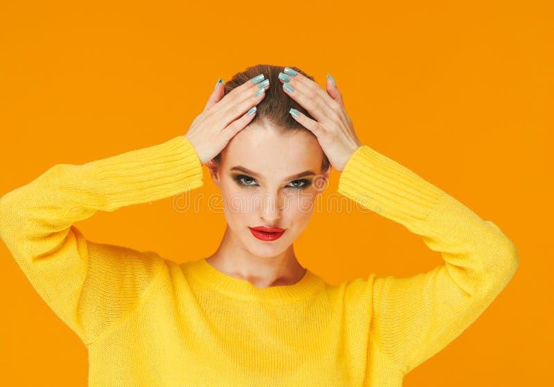 Lèvres rouges de femme colorée de maquillage dans des vêtements jaunes sur les ongles manucurés heureux de fond de mode d'été de  photographie stock libre de droits