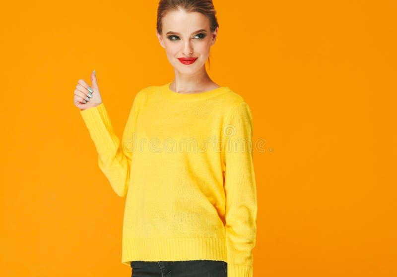 Lèvres rouges de femme colorée de maquillage dans des vêtements jaunes sur les ongles manucurés heureux de fond de mode d'été de  images stock