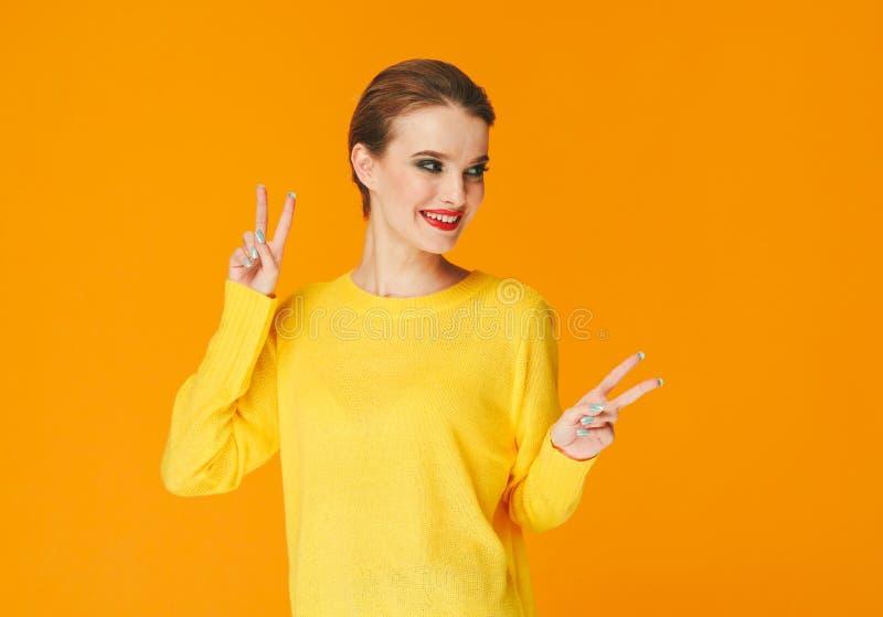 Lèvres rouges de femme colorée de maquillage dans des vêtements jaunes sur les ongles manucurés heureux de fond de mode d'été de  photos stock