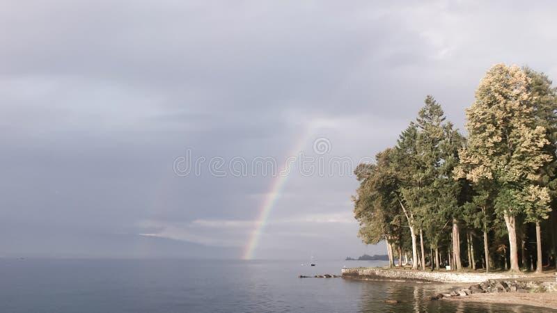 Légèrement effacé arc-en-ciel au-dessus de forêt par un lac photos libres de droits