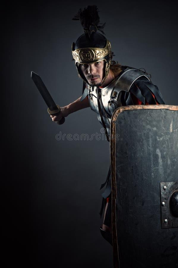 Légionnaire romain brutal avec l'épée et le bouclier dans des mains photographie stock