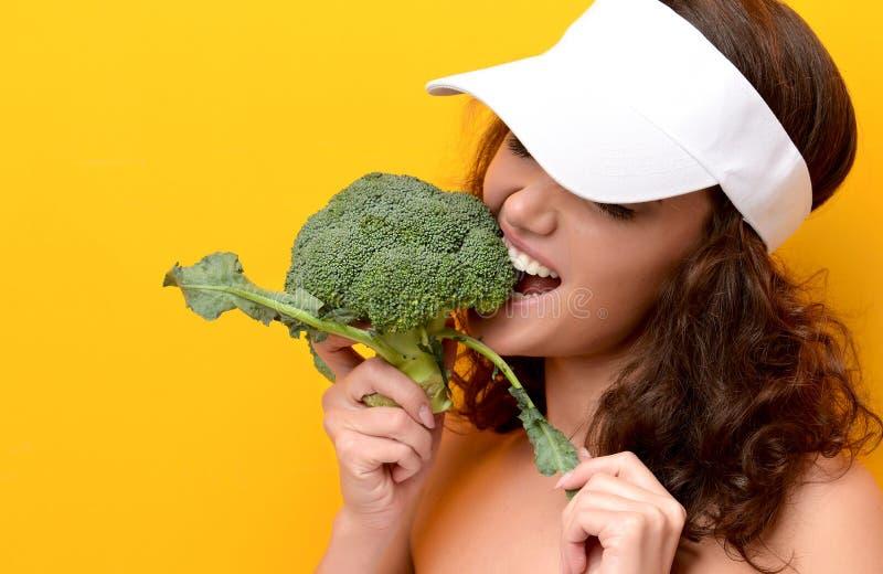 Légume vert frais de brocoli de morsure de jeune femme grand images libres de droits