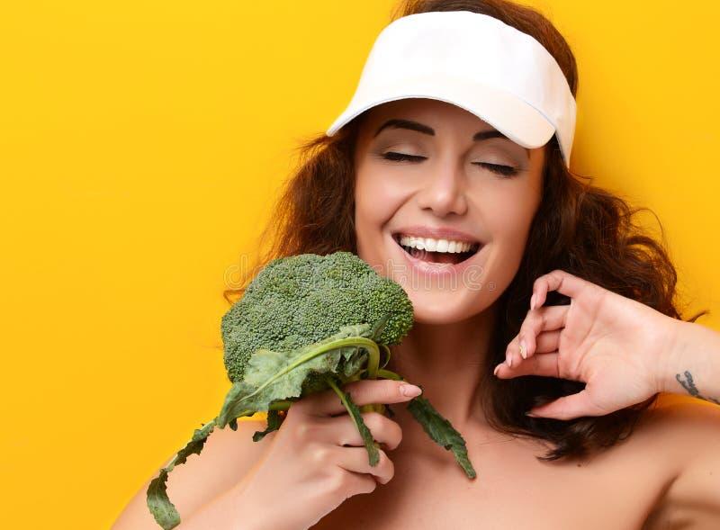 Légume vert frais de brocoli de morsure de jeune femme grand image stock
