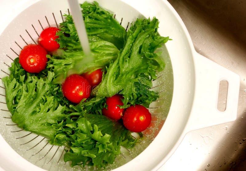 Légumes étant rincés dans une passoire en plastique dans un évier photos stock