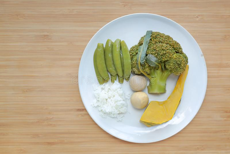 Légumes bouillis brocoli, oeuf, potiron, riz et pois doux dans le plat blanc sur le conseil en bois avec l'espace de copie images stock