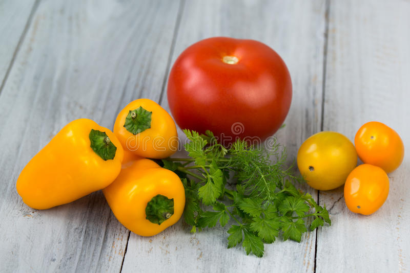 Légumes colorés frais mélangés, tomates-cerises, mini paprika, tomate et herbes fraîches sur un fond en bois images stock