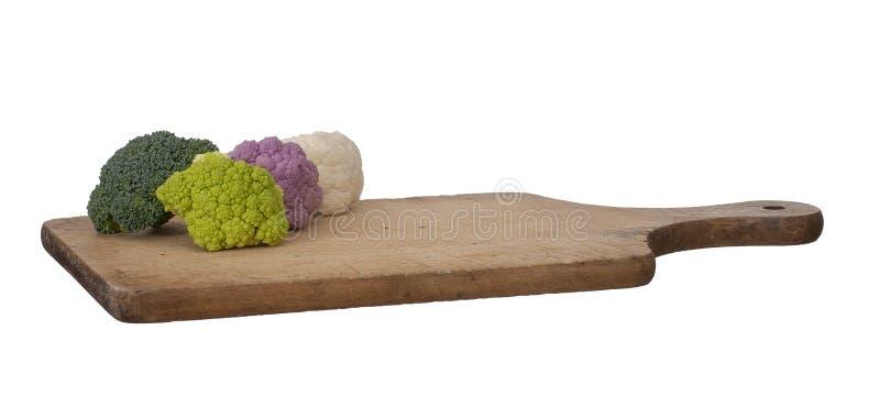 Légumes colorés sur la planche à découper en bois d'isolement sur le blanc Chou-fleur cru, pourpre, blanc et vert, avec frais image libre de droits