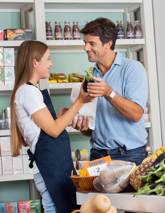 Légumes de achat d'Assisting Man In de vendeuse photographie stock libre de droits