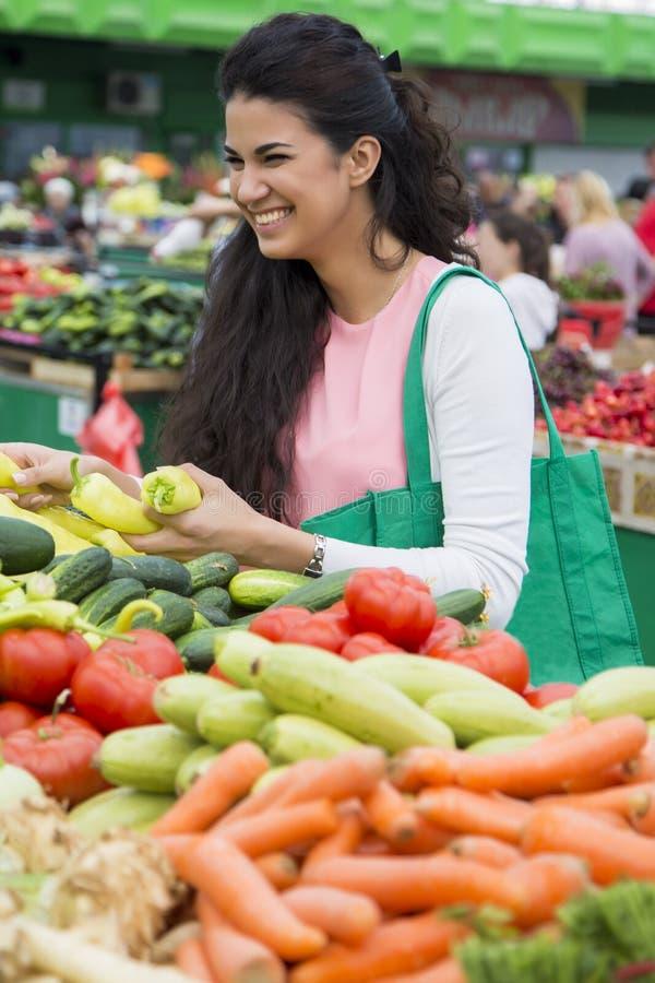 Légumes de achat de femme sur le marché photo libre de droits