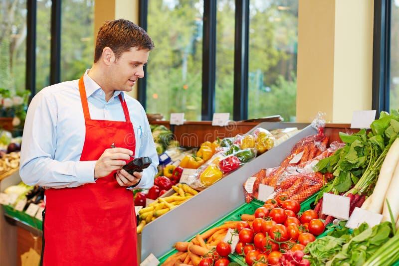 Légumes de commande de directeur de magasin avec le terminal de données images stock