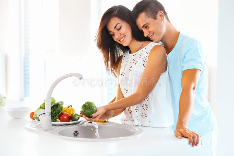 Légumes de lavage de femme, homme l'étreignant dans la cuisine image stock